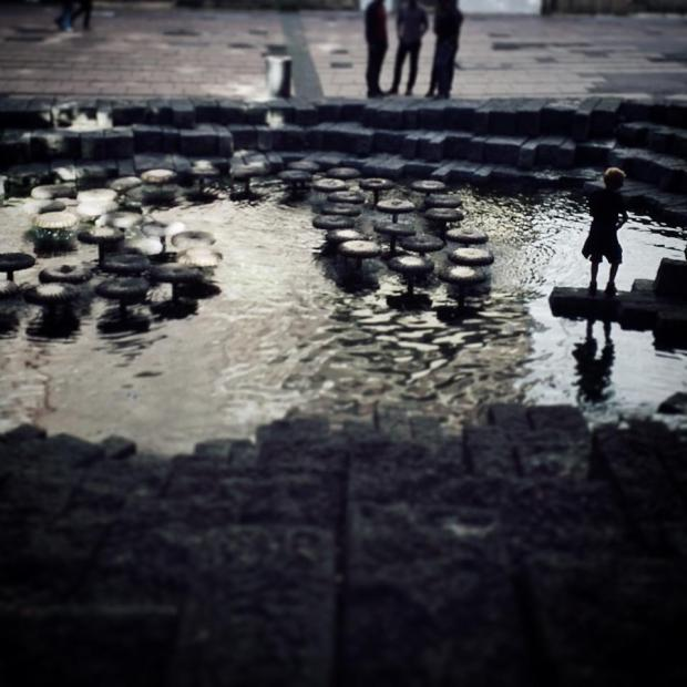 Reflections. Boy stone hopping, near Viktualienmarkt. #Day19 #nataliegeographic